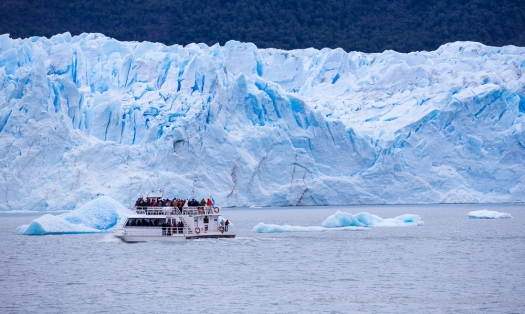 the huge Perito Moreno glacier makes a boat look like a toy